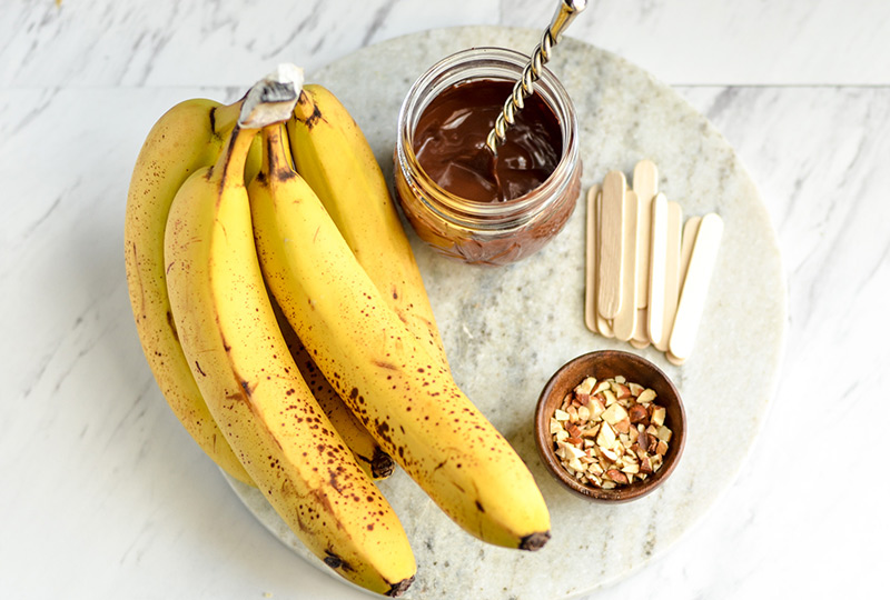 Bananas, melted chocolate, nuts and popsicle sticks
