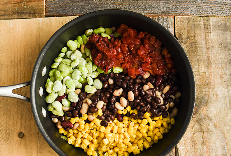 4 types of beans, corn and tomatoes in a pot