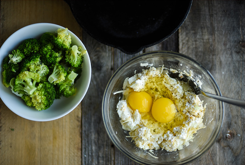 Chopped broccoli in small bowl next to larger bowl with cheese and raw eggs.
