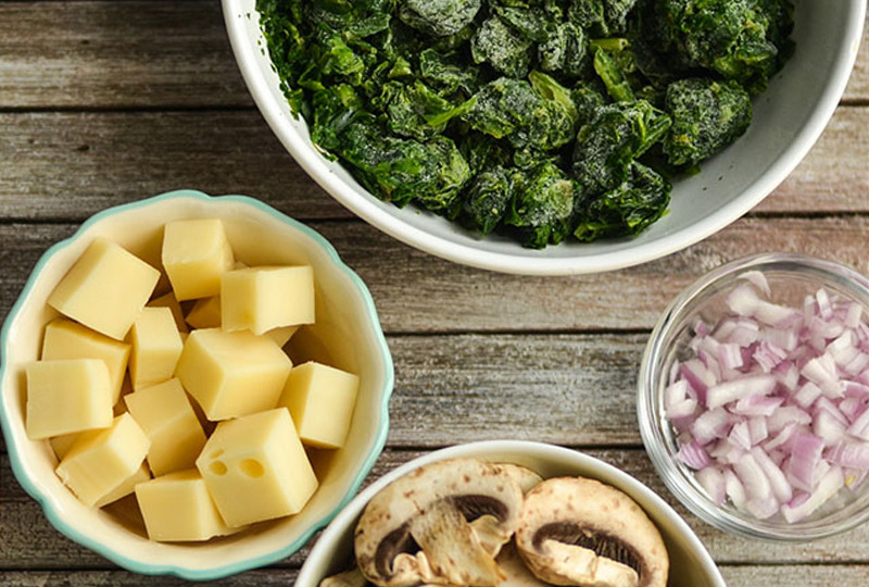 Cubed cheese, spinach, mushrooms and chopped onion for making quiche