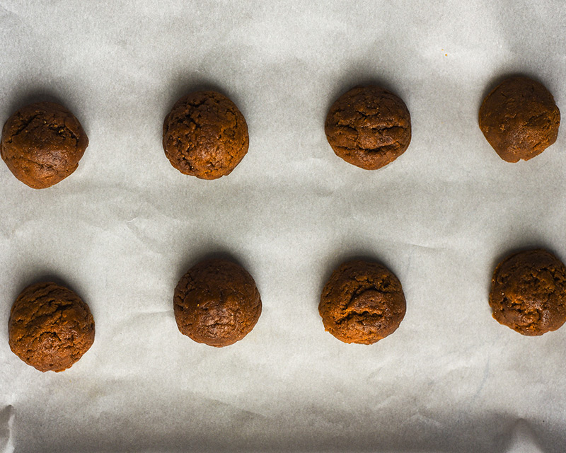 Raw ginger cookie dough rolled in balls on baking sheet.