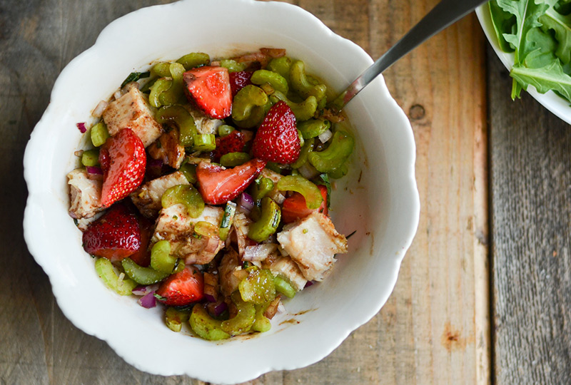 Chicken, celery, onions and strawberries being mixed with glaze in a bowl.