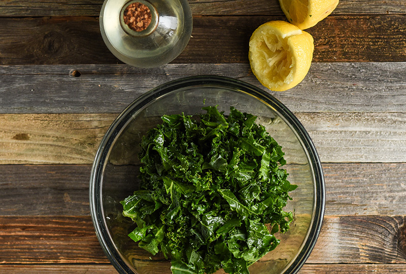Kale in a mixing bowl with freshly squeezed lemon juice