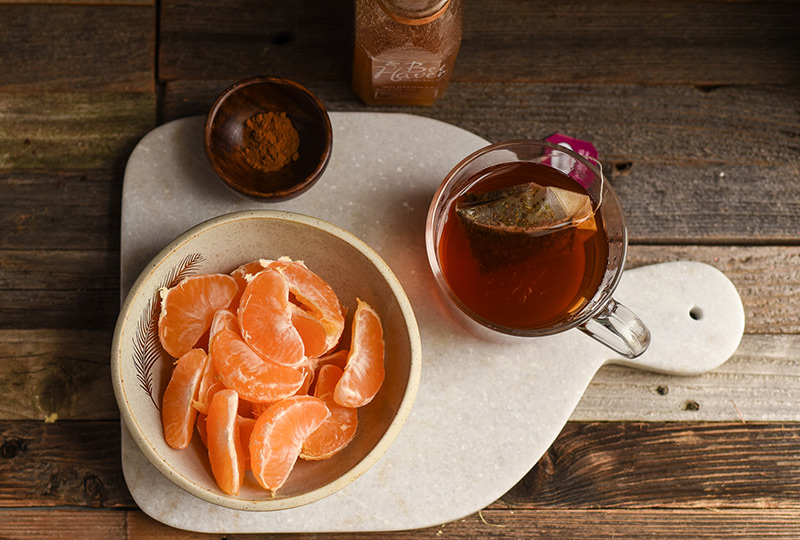 Clementine slices in a bowl, with a cup of hot tea.