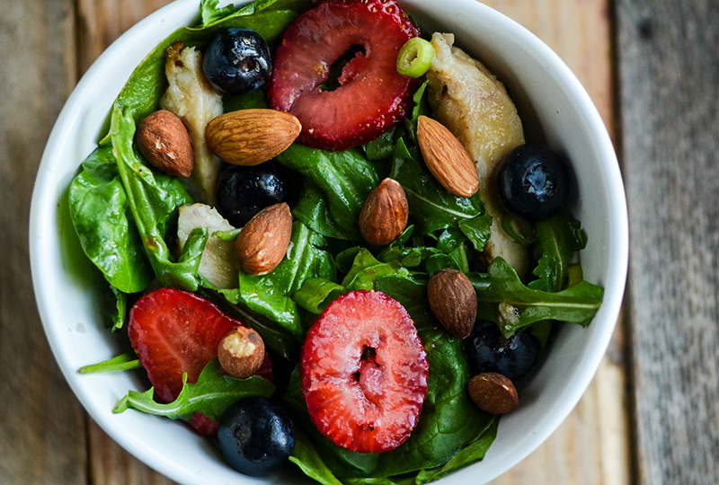 White salad bowl containing salad of leafy greens, berries and chicken