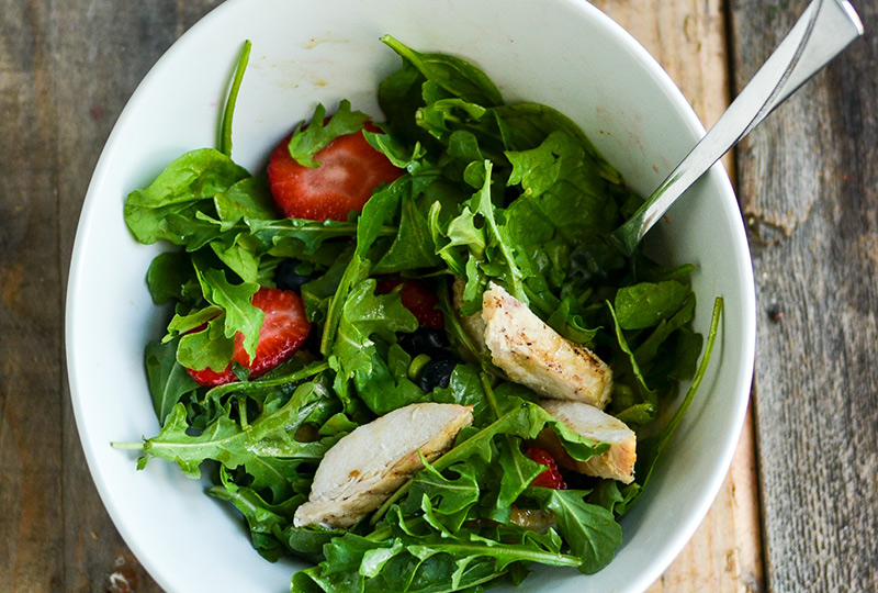 Leafy green salad, chicken and berries in a bowl, tossed with dressing.