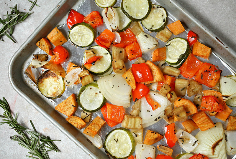 Roasted zucchini, sweet potato, eggplant and peppers on a baking pan.