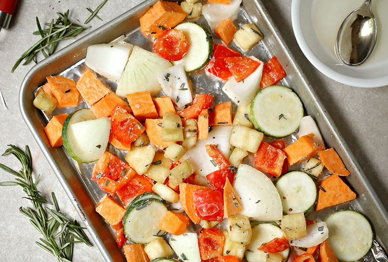 Chopped eggplant, onion, zucchini, red pepper and sweet potato, tossed on a baking pan for roasting.