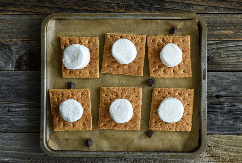 Graham crackers on a baking pan topped with marshmallows