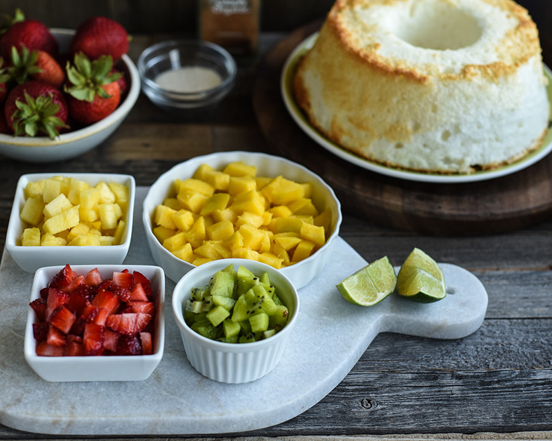 Chopped fruit in bowls and a plate of angel food cake