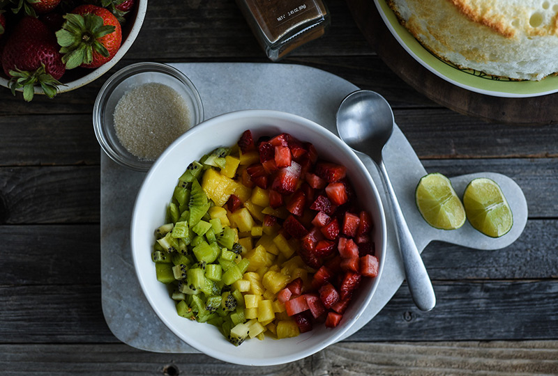Chopped strawberries, pineapple and kiwi in a mixing bowl, with a small bowl of sugar nearby.
