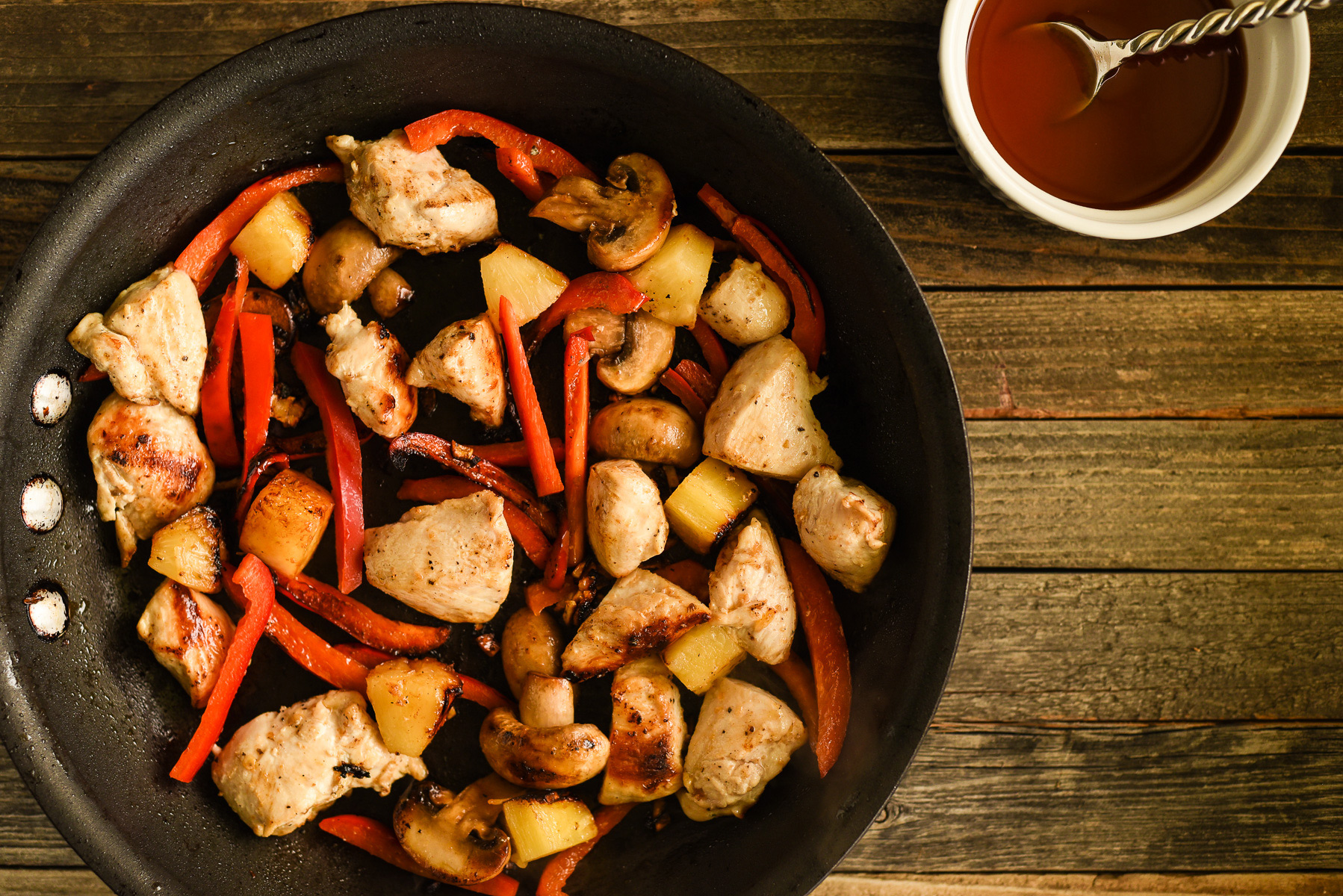 Chopped chicken, pepper, mushroom and pineapple, stir-fried in a skillet