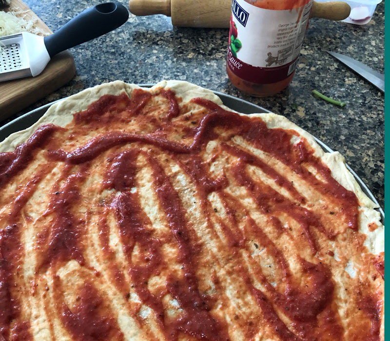 Tomato sauce spread over raw pizza dough.