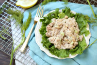 Light tuna salad on a bed of greens served on a small white plate.