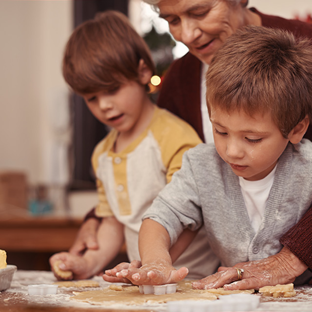 Two young boys baking cookies with their grandmother