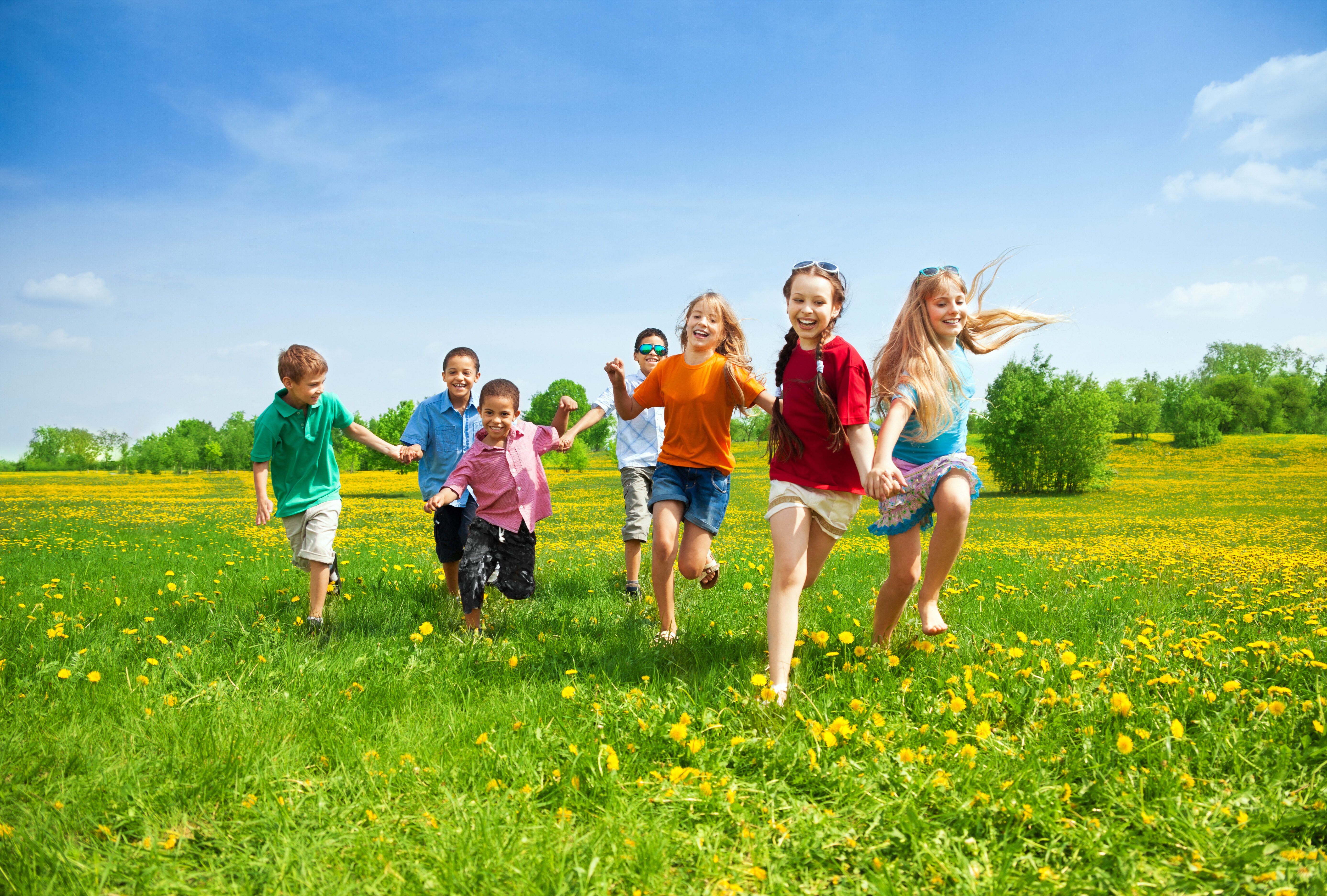 Group of children running and playing during summer time.