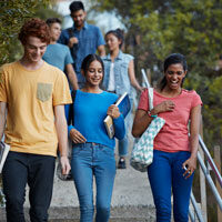A group of teens walks down a set of stairs outside a school.