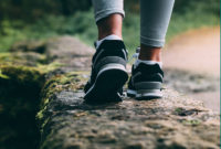Closeup of feet of person walking outdoors on a stone wall