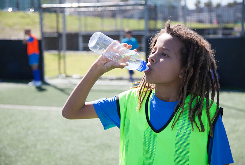 Boy drinking water during soccer practice