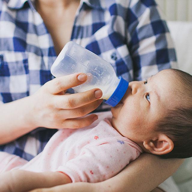 A mother feeds her infant a bottle of formula