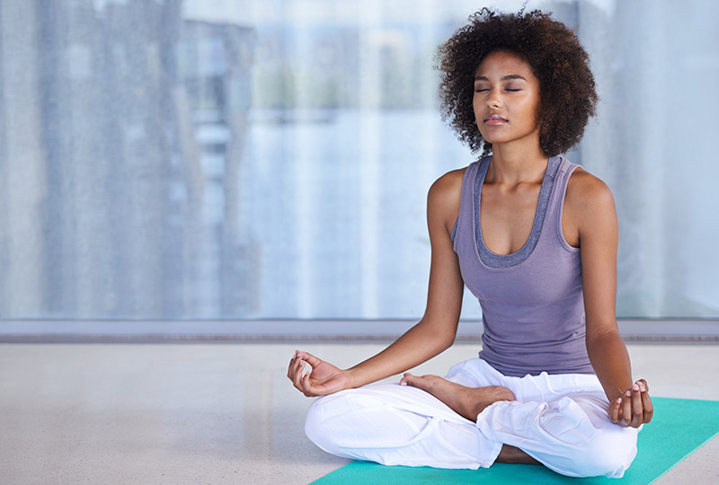 Woman sits in lotus position doing yoga