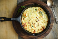 Cast iron pan containing baked broccoli-cheese casserole