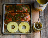 Salmon fillets and pineapple rings on a baking sheet
