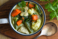 Closeup photo of chicken and vegetable Thai soup in a bowl.