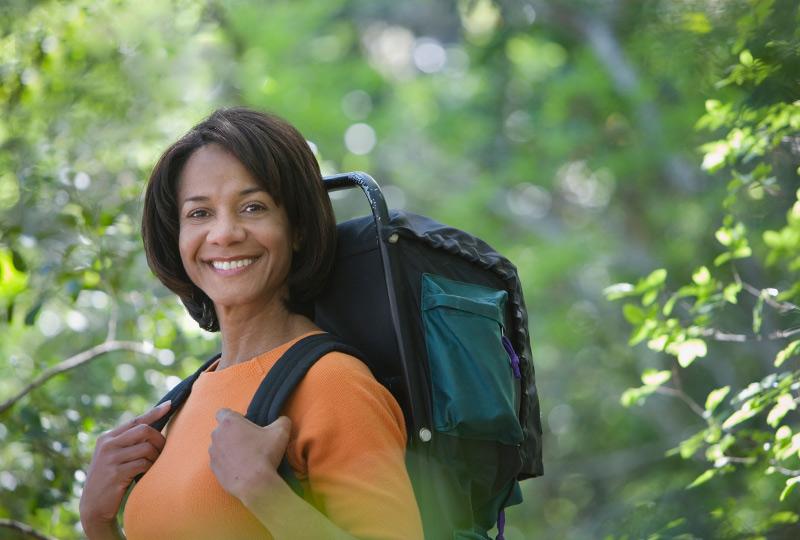 Black woman walking in woods wearing backpack
