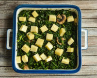 Diced cheese, spinach and mushrooms in baking pan