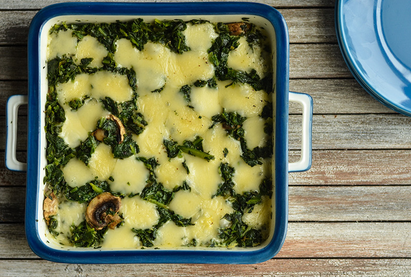 Square casserole pan containing spinach cheese quiche
