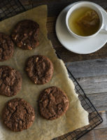 Tray of triple chocolate cookies resting next to a cup of tea.