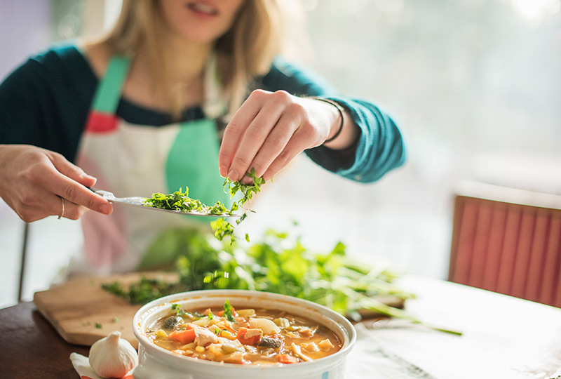 A woman sprinkles fresh herbs into a bowl of soup.