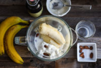 Bananas, yogurt, almonds and a blender with ice cubes