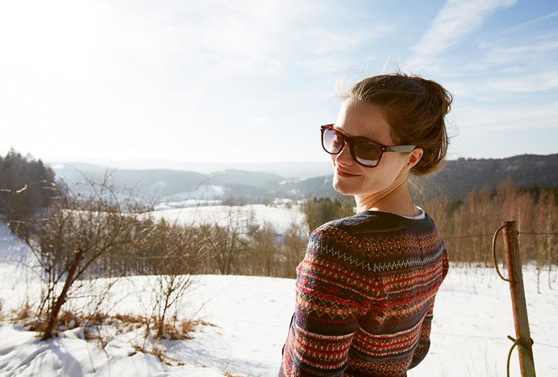 Woman standing in a snowy field wearing sunglasses