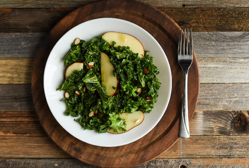 Massaged kale salad with apple slices, served in a bowl
