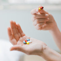 Woman holds several pills in her palm