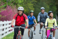 Family of four biking on a trail together in spring