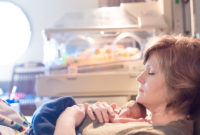 Woman rests with newborn laying on her chest