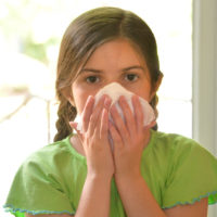 Girl blowing her nose into a tissue
