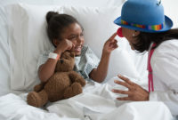 A girl in a hospital bed gets a visit from a clown