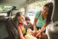 A woman buckles a grade-school-aged girl into a car seat.
