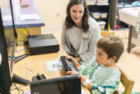 A Vanderbilt child life specialist plays a computer game with a patient