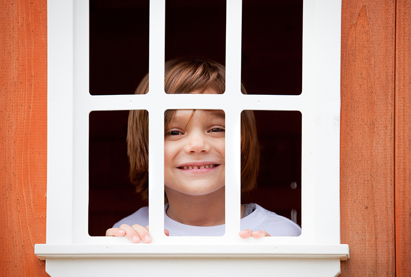 A young boy smiles as he peeks though the window of his playhouse.