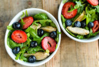 Two bowls with salads of leafy greens, berries and chicken