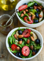 2 bowls filled with salads of leafy greens, berries and chicken.