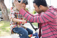 A father helps young son put on a bike helmet