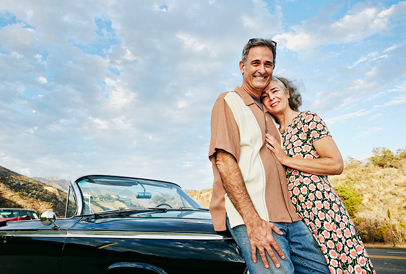 Older couple pose next to vintage sports convertible car.