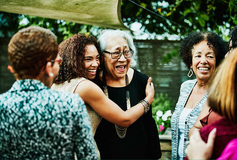 A young woman hugs an older woman in a backyard full of people.