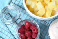 A bowl of pineapple chunks, a bowl of raspberries and a bowl of yogurt, ready to make parfaits.